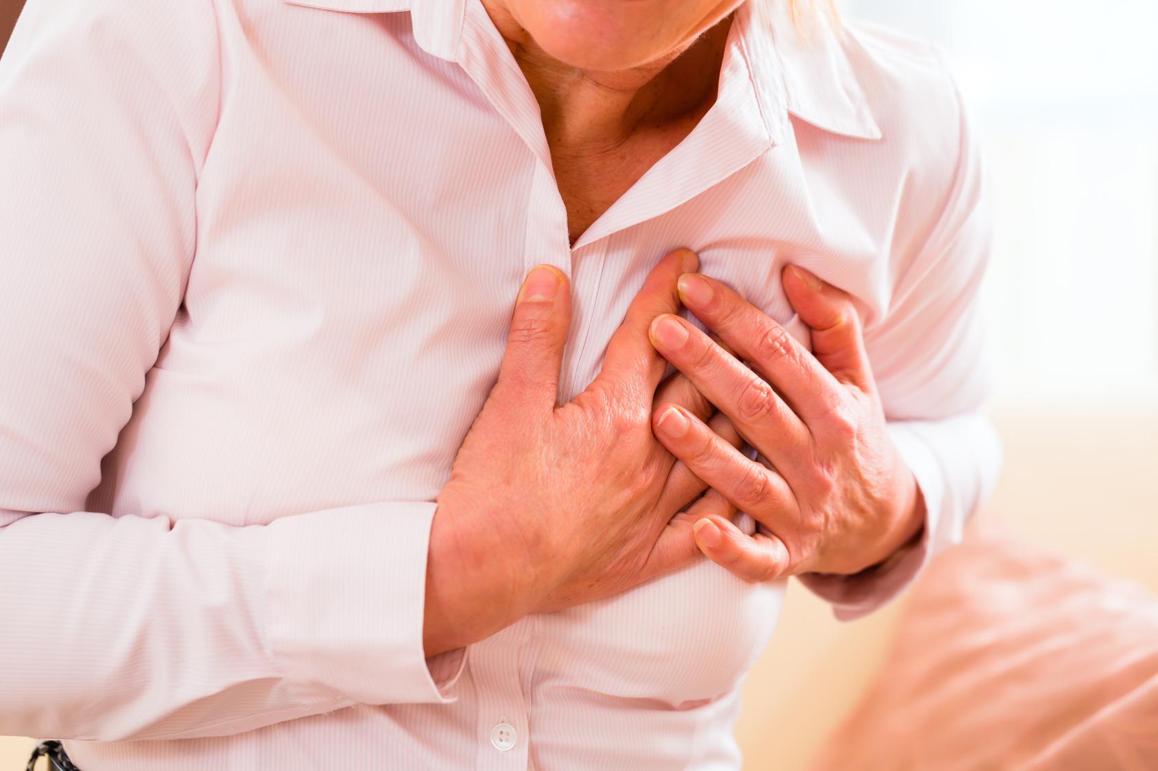 frau-herzinfarkt-zu-hause-seniorin-schmerz-in-brust-rosa-hemd