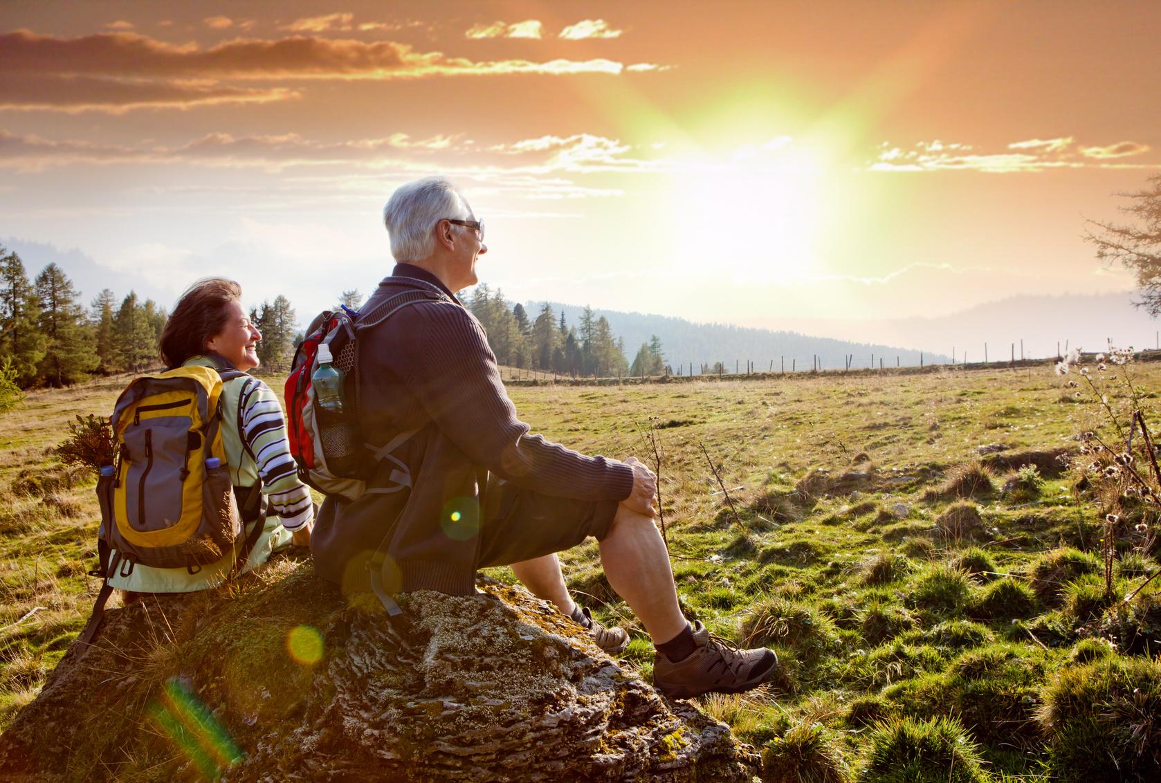 freizeitaktivitaet-senioren-wandern-rucksack-sonnenuntergang-pause-huegel-weide