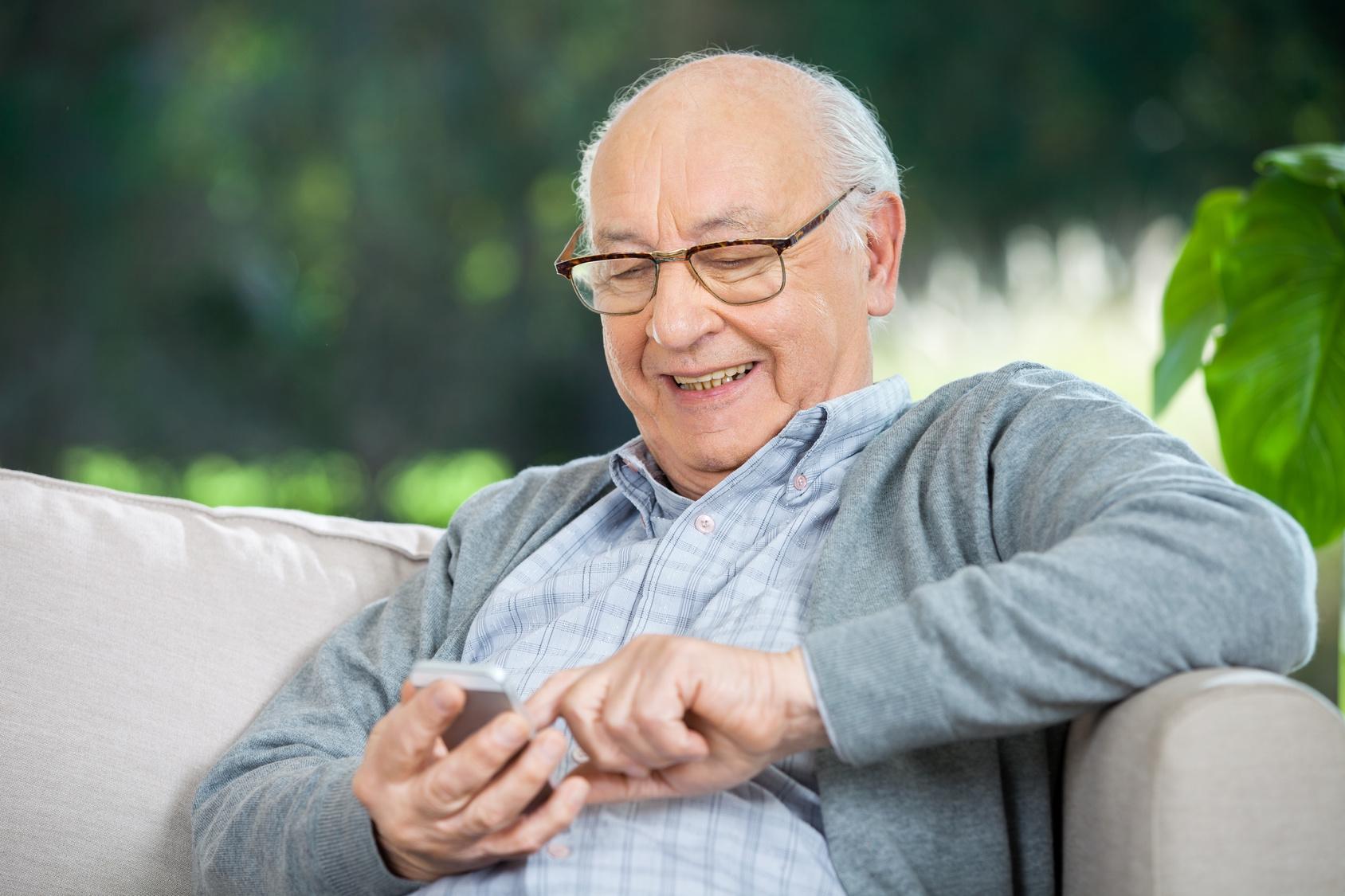 senior-mit-brille-auf-der-couch-handy-seniorengerecht
