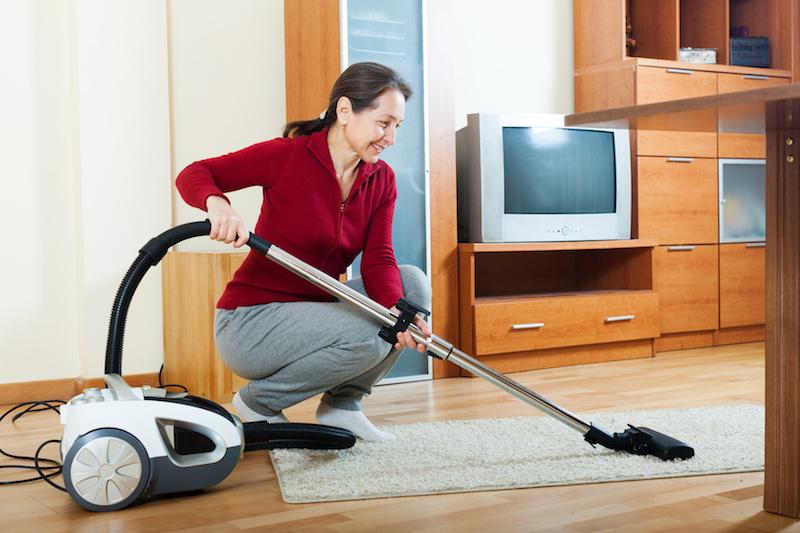Haushaltshilfe-mit-rotem-Pullover-und-Staubsauger-saugt-weissen-Teppich-im-Wohnzimmer